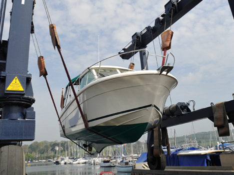 Outboard boat in travel lift slings